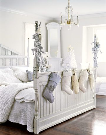 white bedroom with stockings hung from the bed frame