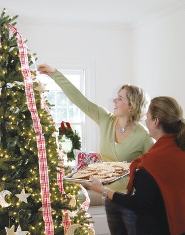 two women hanging cookie ornaments from a tree