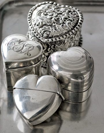 four silver heart shaped ring boxes on a silver platter
