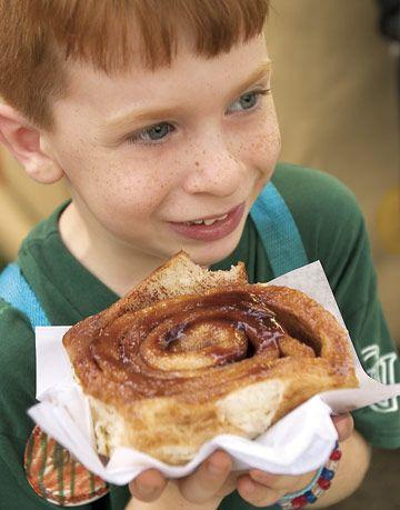 little boy holding bit cinnamon roll