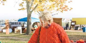 woman in orange jacket looking at chairs at an outdoor antique market