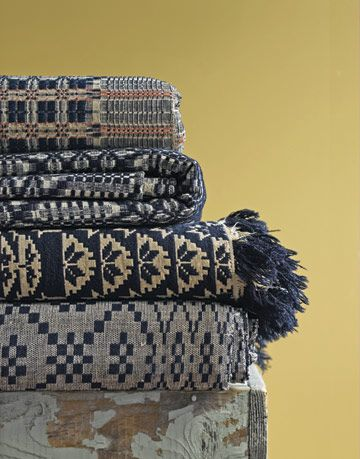 stack of antique blankets with different patterns