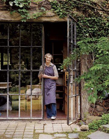 woman standing inside the doorway of a vine covered studio