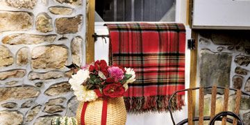 small outdoor table decorated with plaid throws