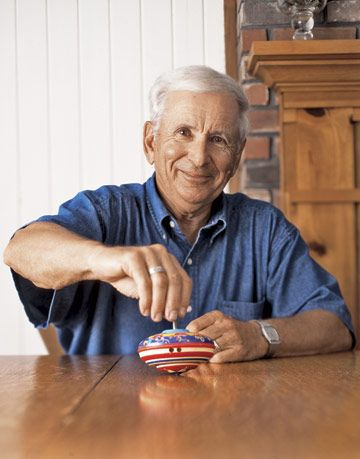 man smiling and holding a spinning top on a table