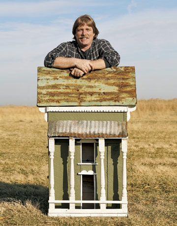 man standing behind giant birdhouse in a field