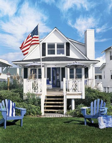 blue and white beach house with american flag and blue adirondack chairs