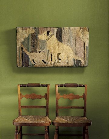 hooked rug of dog and cat on a wall above chairs
