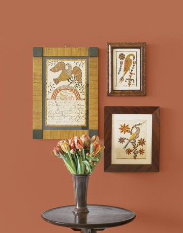 three folk prints in frames on a rust colored wall