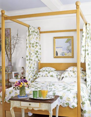 a bedroom with a for poster bed with spring colored bedding