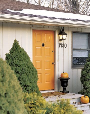 the front of a house with an orange door and pumpkins