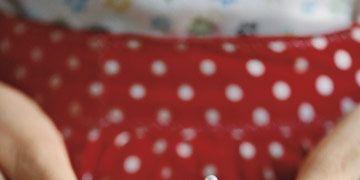 hands holding a small polka dot pin cushion