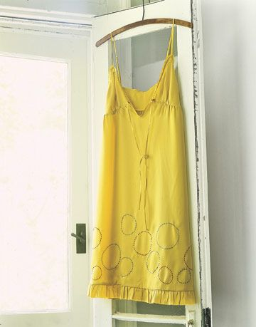yellow dress with sewn polka dots on the bottom hanging from a door