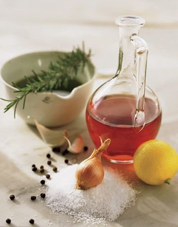 vinegar in a glass jug next to a lemon and garlic and herbs