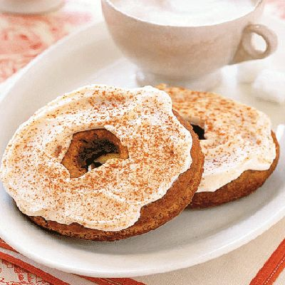 two doughnuts with vanilla icing sprinkled with cinnamon on a plate