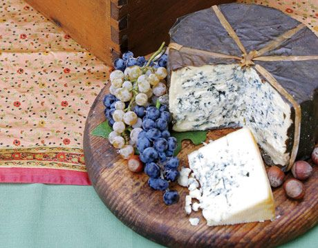 large wheel of blue cheese on a platter with grapes