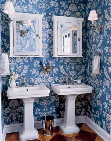 twin white pedestal sinks in blue and white floral wallpapered room
