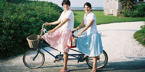 two women in skirts on a tandem bicycle