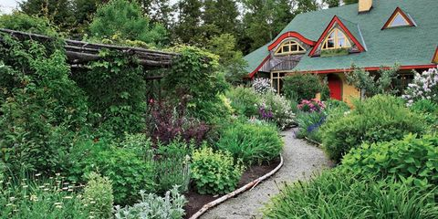 cottage with yellow and red trim and lush garden