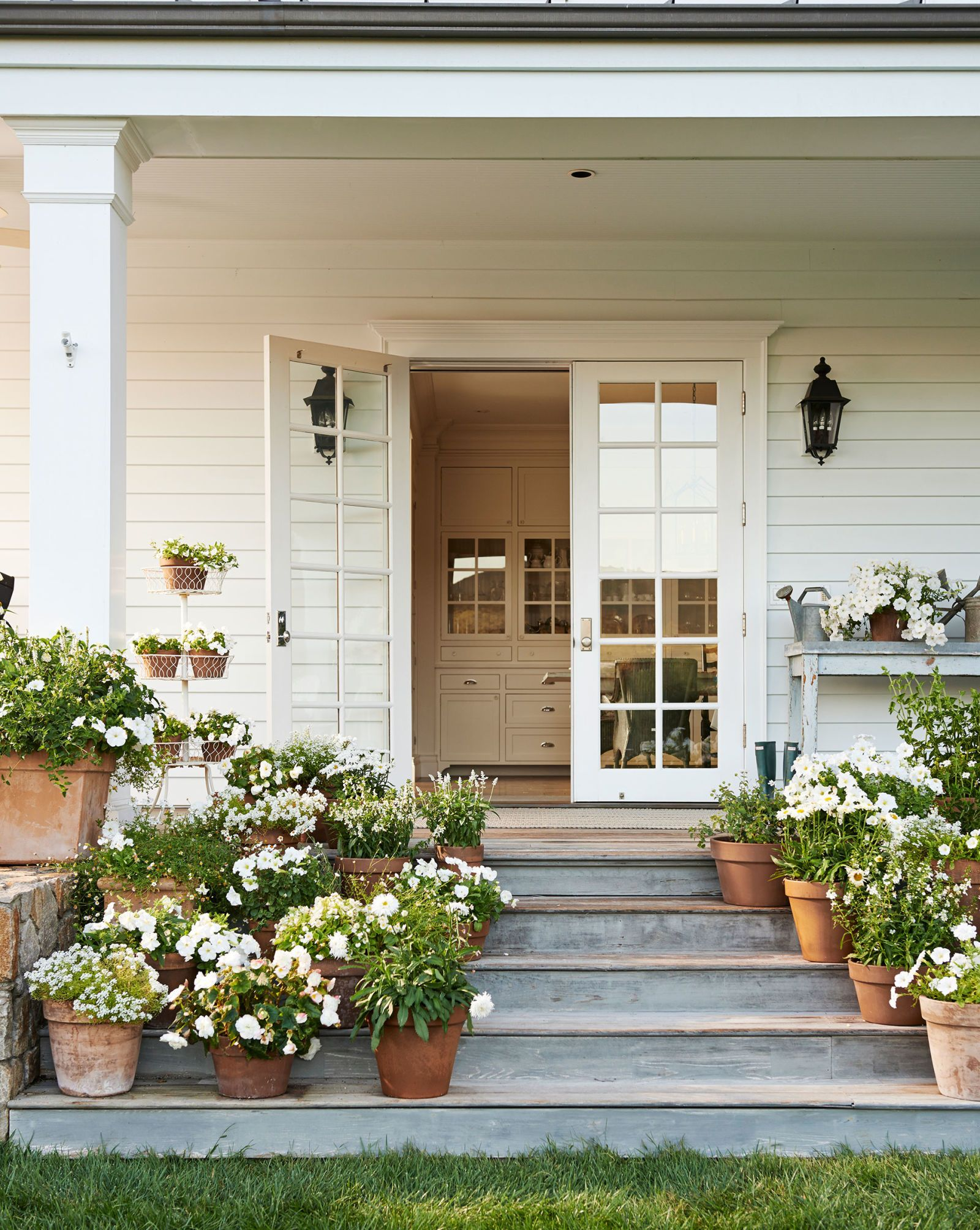 Charming back porch off farmhouse kitchen with wide steps massed with terracotta pots of flowers. #porch #decoratingideas #steps #farmhouse