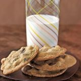 chocolate chip cookies on a plate next to a glass of milk