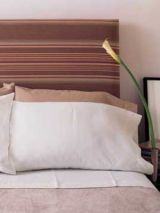 a padded striped fabric headboard on bed with pillows