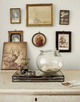 fishbowl with trophy collectibles and picture frames hanging on the wall