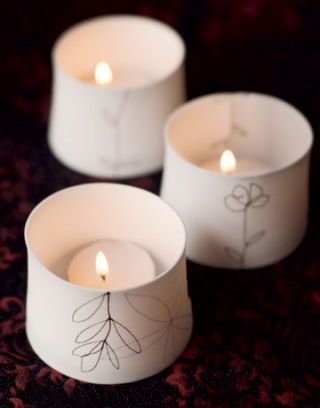 Three white tealight candles with leaf designs