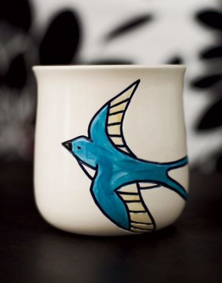 a white tea cup with painted blue swallow