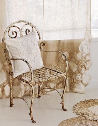 a cream iron chair by a window, with doily-embellished drapes and an off-white pillow with doily sewn on