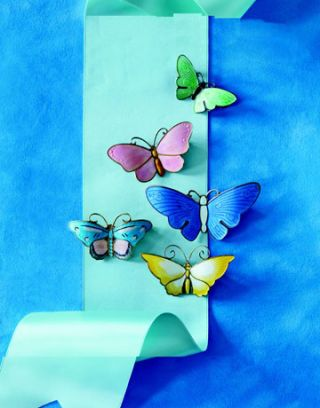 colorful enameled butterfly pins on blue background