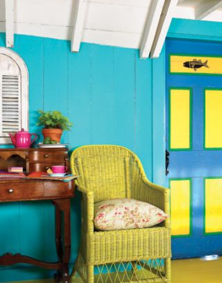 blue walls, painted door, and a wicker chair