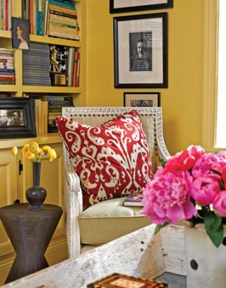 white chair with tan padding and red and white pillow in yellow room