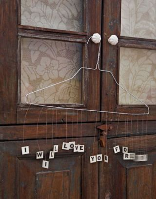 hanger on a wooden door with a message made of dangling letters