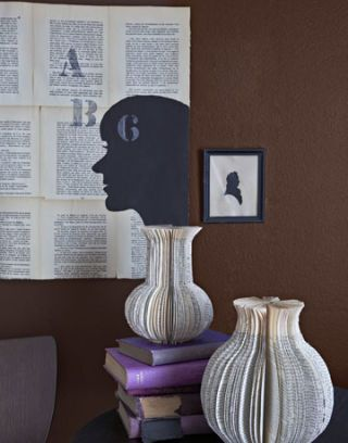 two paper vases made from books and a book page wall hanging with profile