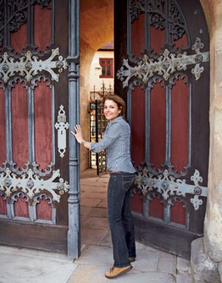 woman opening giant doors to a castle