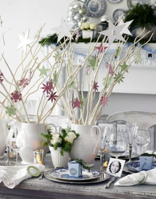 white branches with paper star ornaments in pitchers