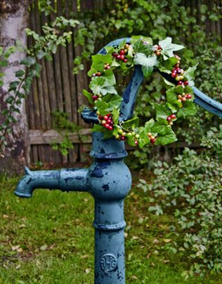 small ivy and berry wreath on a garden faucet