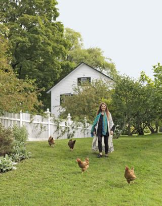 woman with roosters in a yard