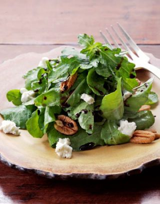 plate of salad with cheese and walnuts