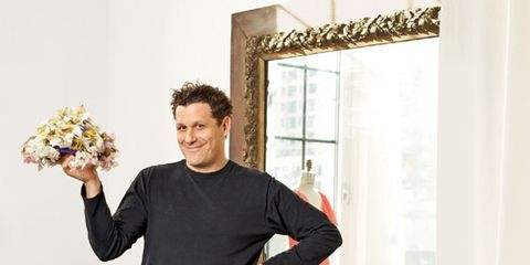 isaac mizrahi dressed in black holding a vintage hat bouquet