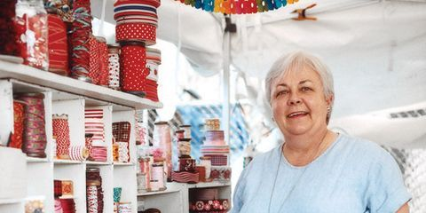 susan gower standing alongside shelves of red trim and ribbons