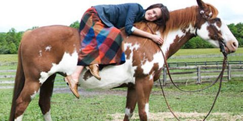 woman in country style clothing on horse