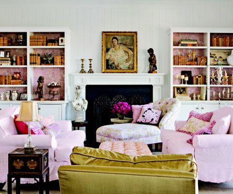 living room with white walls and pink accents tempered with gold touches
