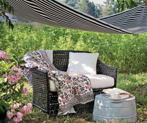 faux-wicker love seat with quilt under an awning