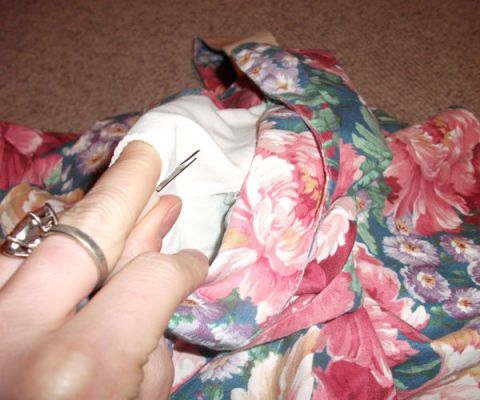 seam rippers removing white fabric from floral dress