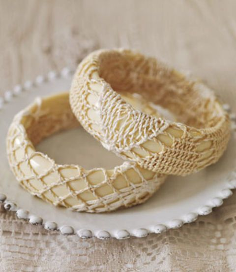 two cream plastic bracelets covered in doilies on a plate