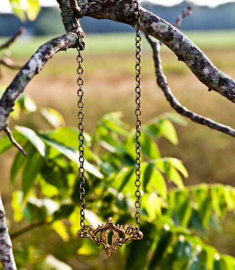 brass keyhole necklace hanging on a tree branch