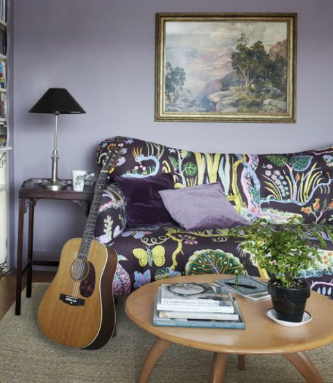 living room with purple walls and purple print sofa