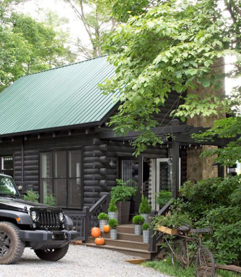a log cabin painted a dark brown with a green roof and a jeep parked out front